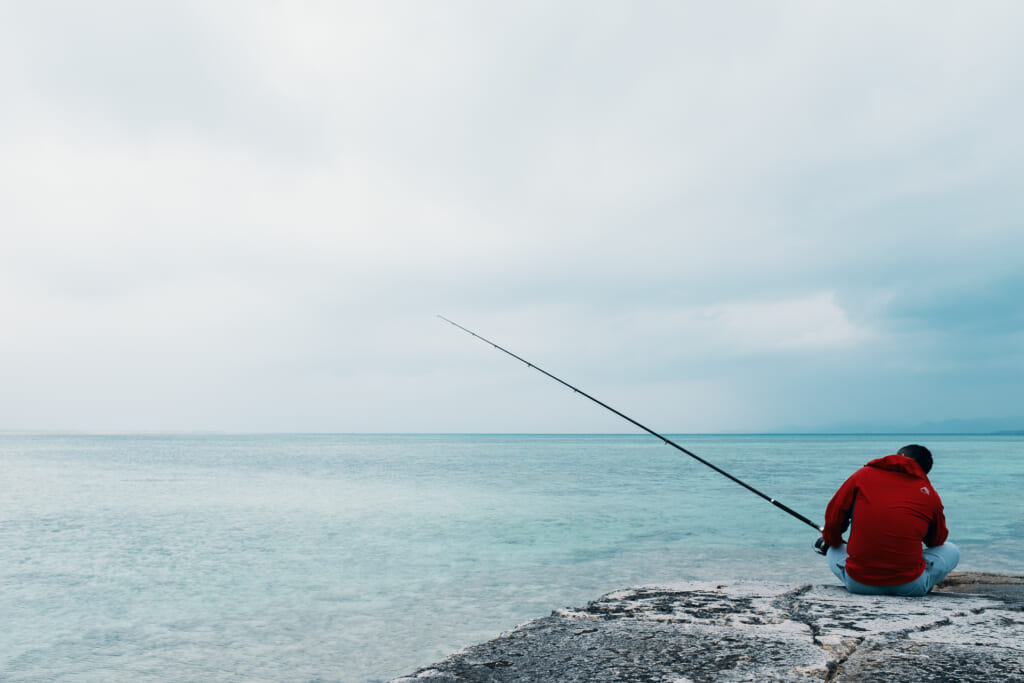 a fisherman waiting for his first catch of the year in taketomi island