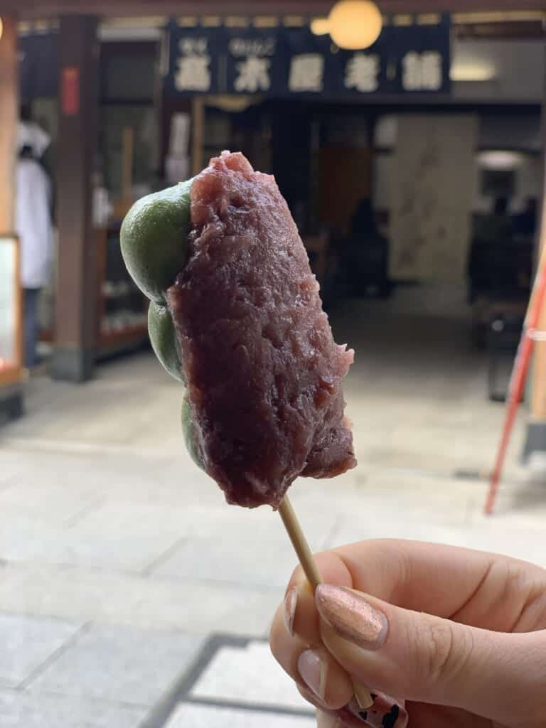 A delicious stick of kusa dango, a stick of green rice balls topped with a thick red-bean paste.