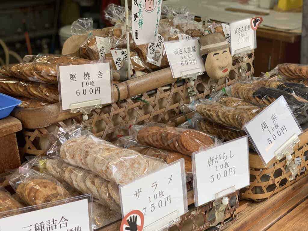 Multiple baskets filled to the brim with different flavors of Japanese rice crackers at Asanoya.