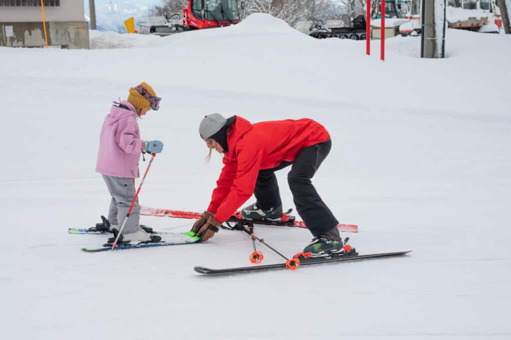 instructor helps child learn to ski at madarao mountain resort in nagano