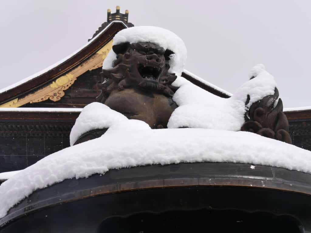 stone lions covered in snow at zenkoji temple