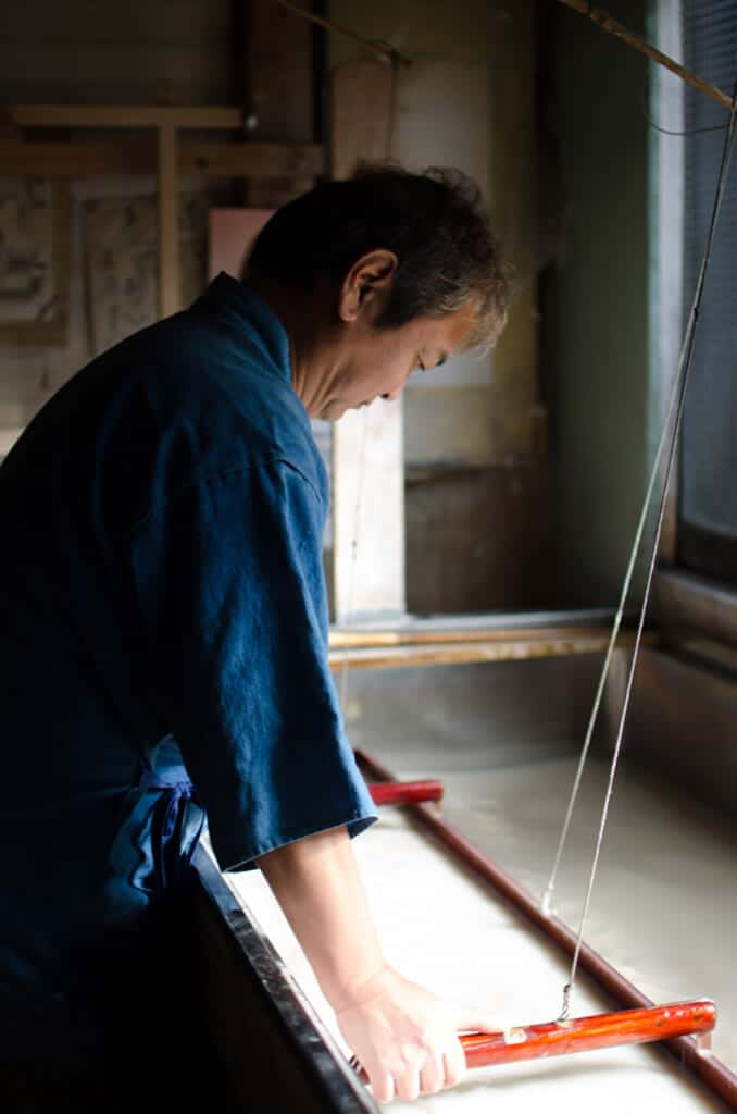 Japanese artisan making washi paper in his workshop
