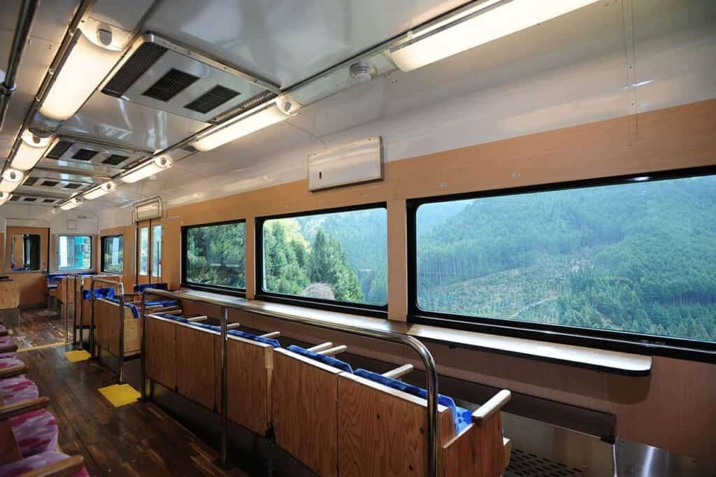 Interior of Japanese Tenku train, with seats facing view of mountain landscape through large windows