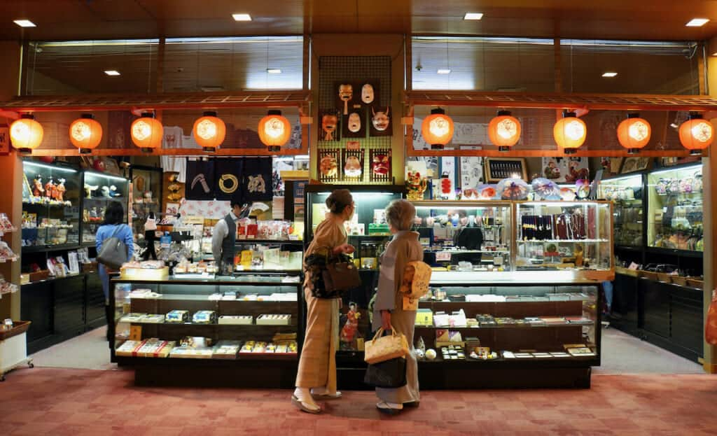 Two women wearing kimono in front of National Theatre shop