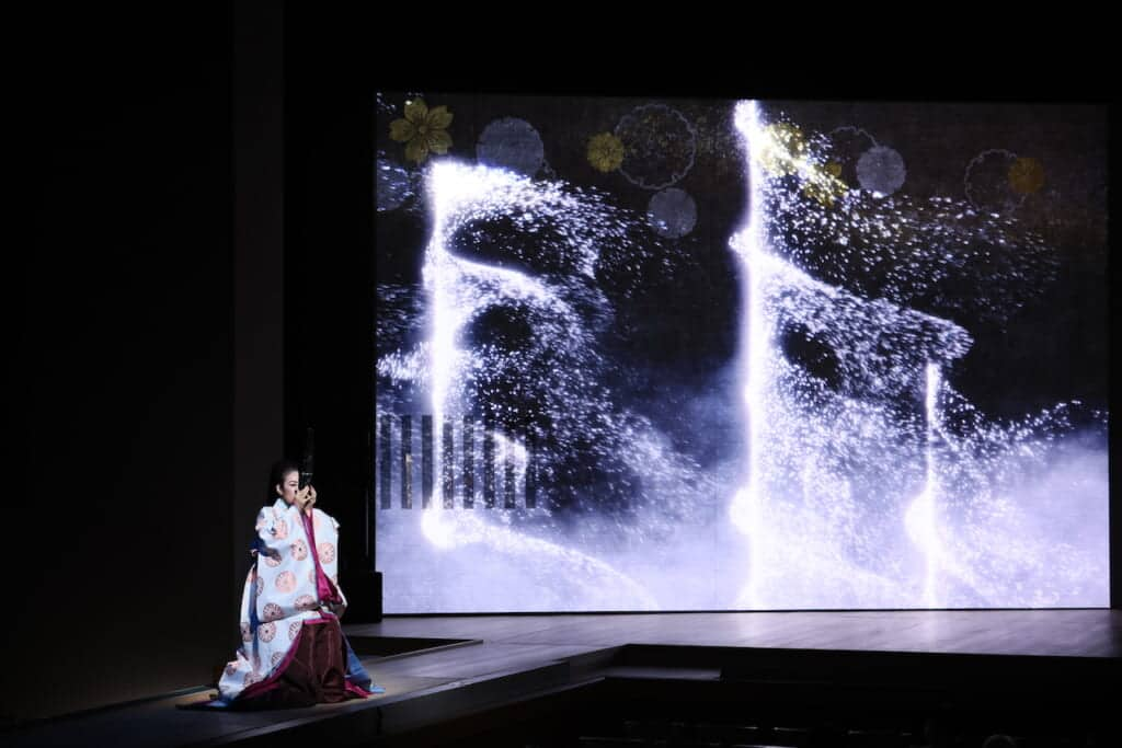 Woman playing Japanese sho instrument on stage for Kabuki performance