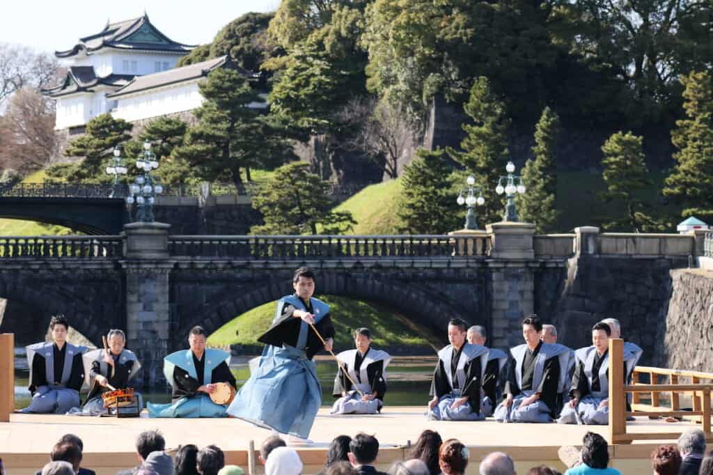 Noh dancer on stage in front of bridge and palace