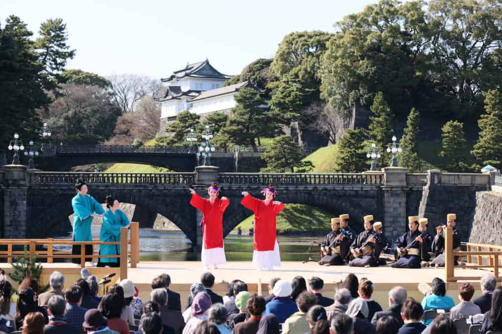 2 dancers in red, 2 dancers in blue on stage in front of bridge and Japanese palace