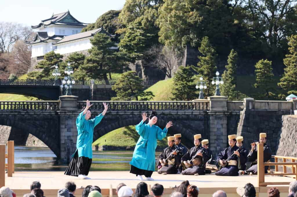 traditional Japanese dance with 2 Okinawan dancers in blue on stage in Japan