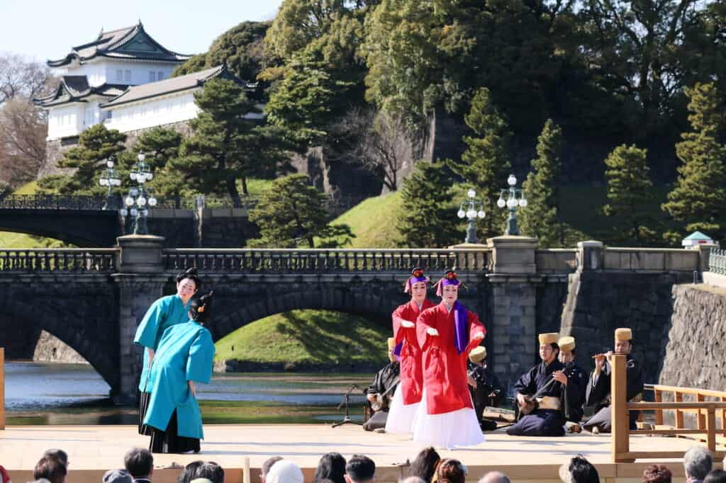traditional Japanese dance, 2 dancers in red, 2 dancers in blue on stage in front of Imperial Palace in Japan