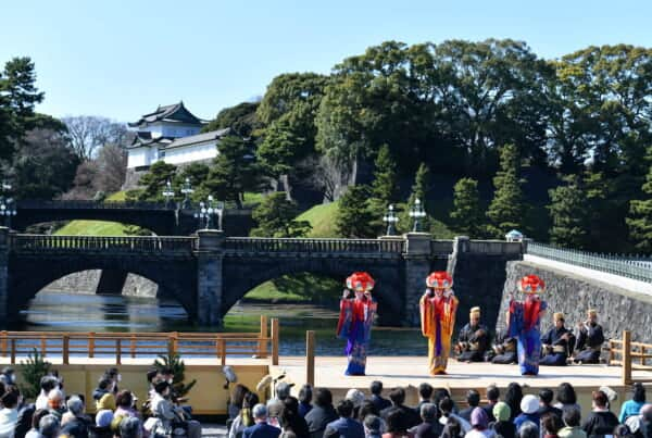 Three dancers on stage in front of a bridge and Imperial Palace