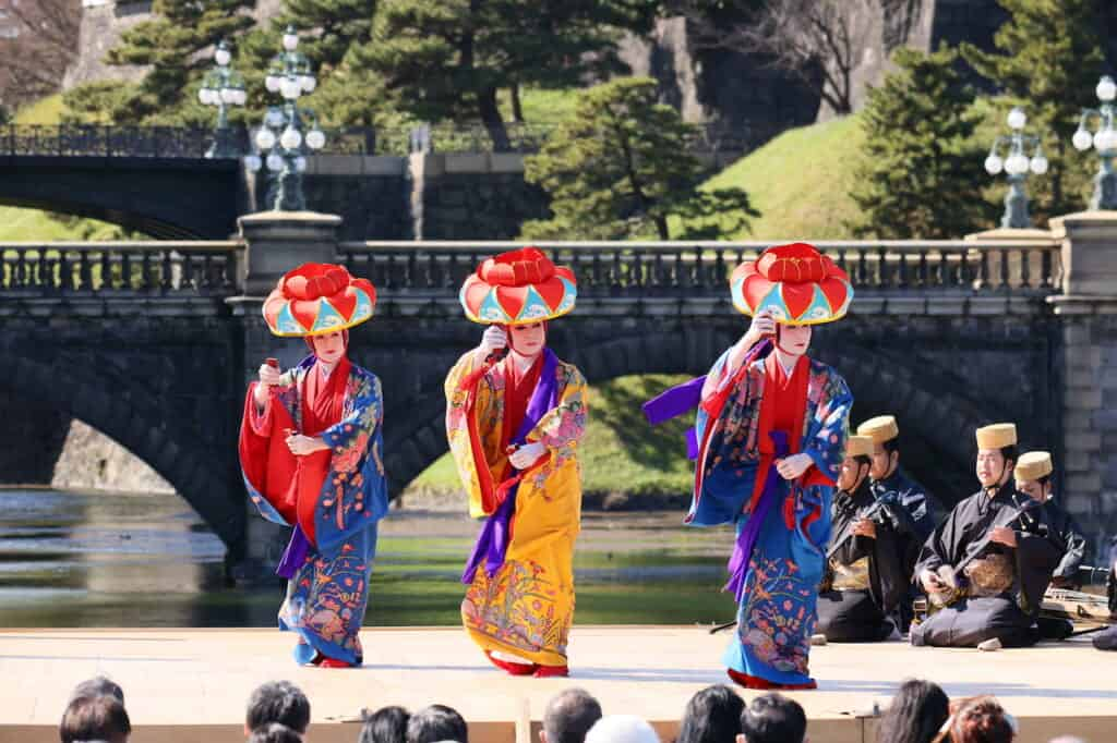 3 traditional Ryukyu dancers in bright costumes in Japan