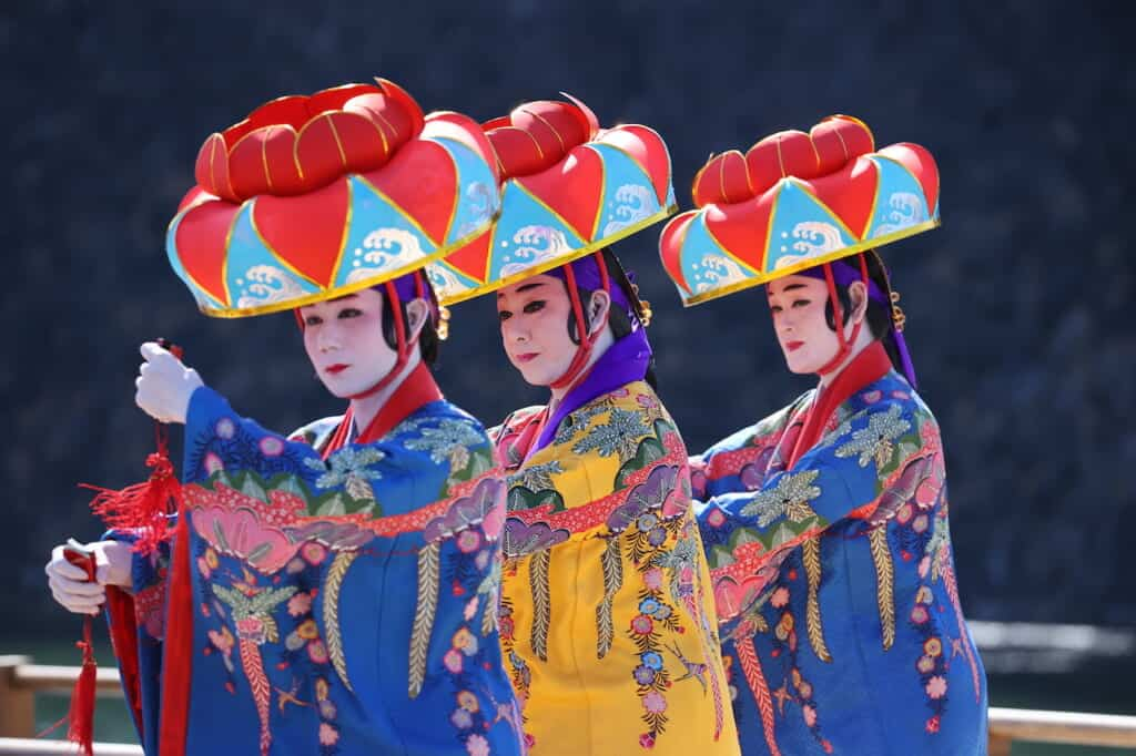 3 traditional Okinawa dancers wearing bright hats in Japan