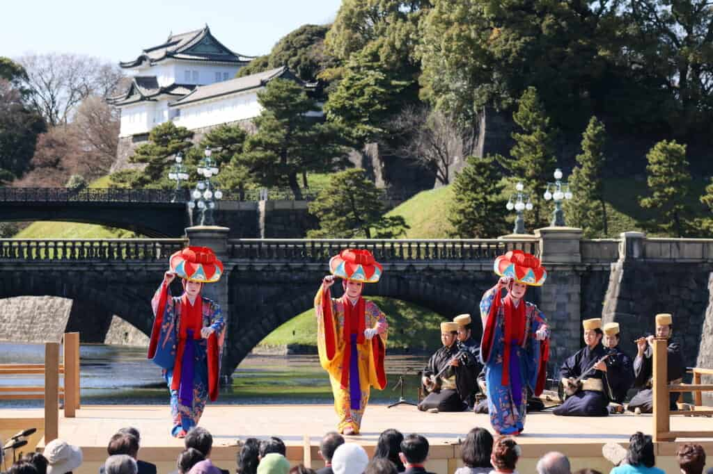 3 traditional Okinawa dancers in front of Double Bridge and Imperial Palace in Japan