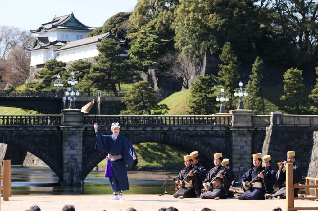 Male dancer holding flag on stage in front of bridge and palace