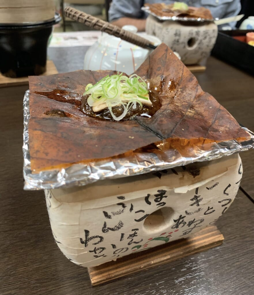 Traditional Japanese meal withHoba miso on a magnolia leaf cooking over a tabletop grill