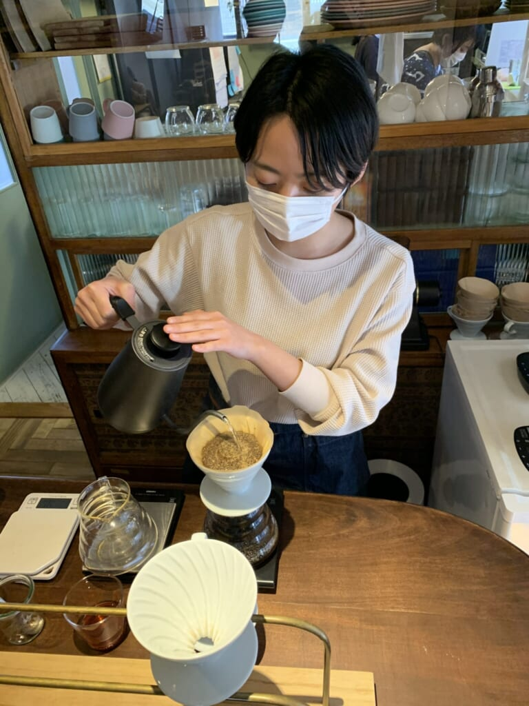 a young man pours hot water to infuse a therapeutic tea in Japan
