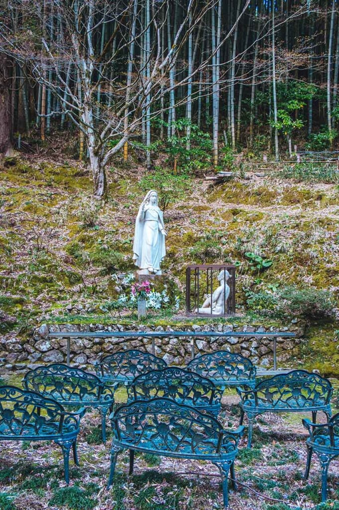 White Christian statue in the Japanese woodland
