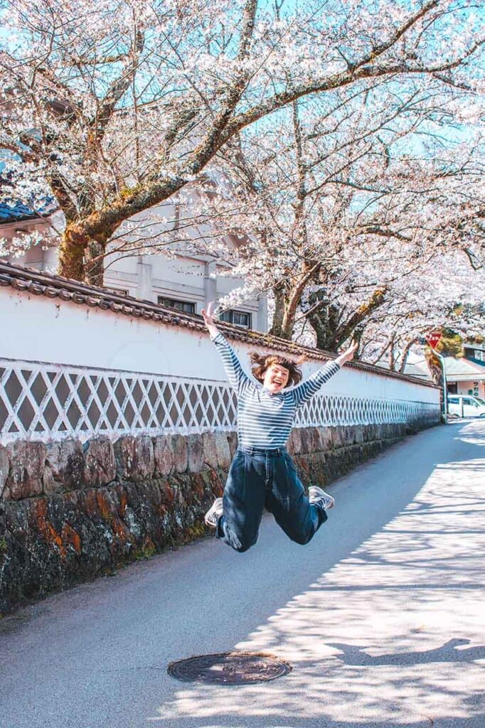 woman jumping in front of cherry blossoms in Japan