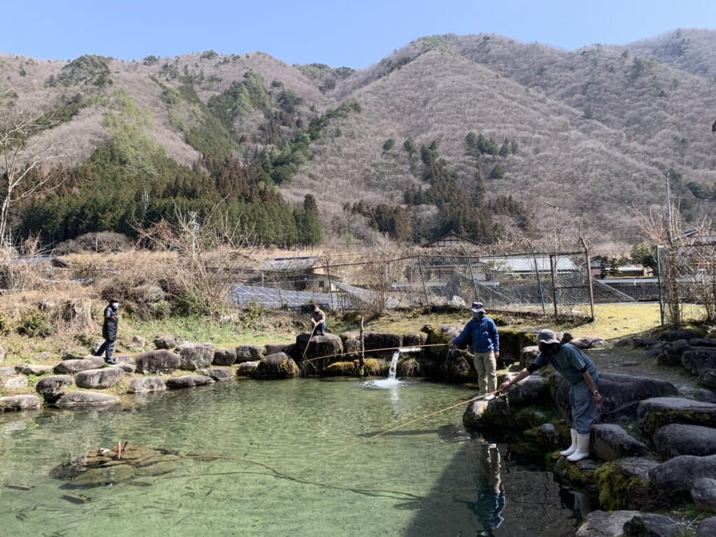 people fishing in a pond in Japan