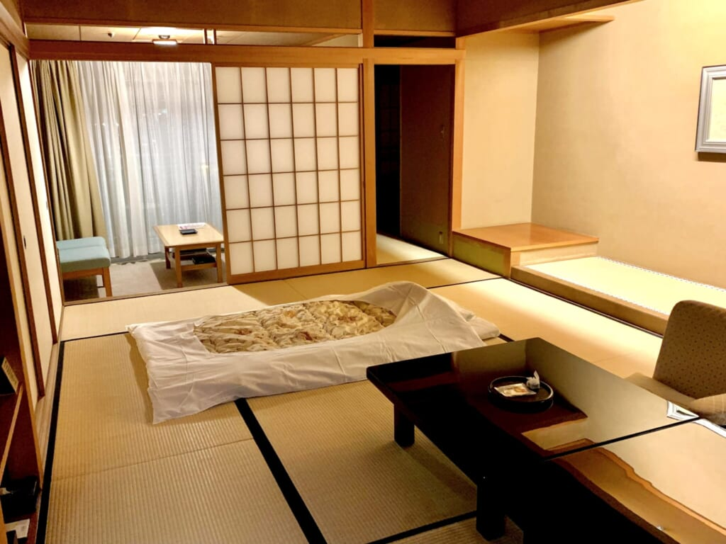 large tatami room with futon in traditional JApanese ryokan inn