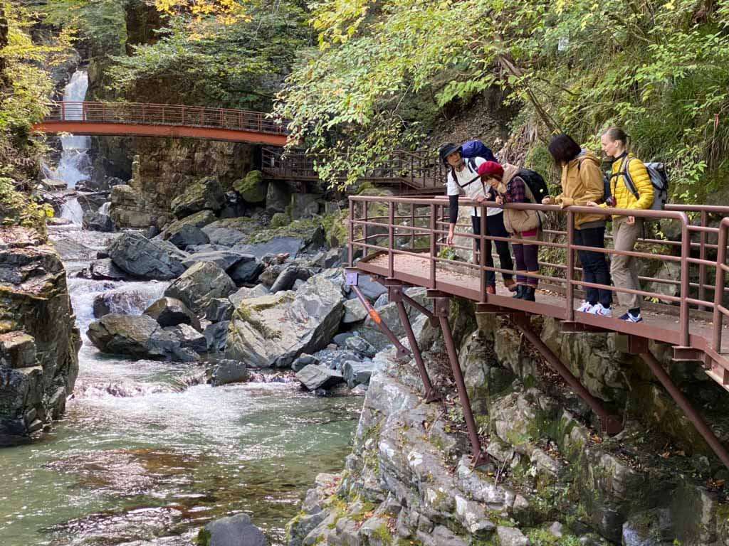 people look out over a river near a waterfall while hiking in Japan
