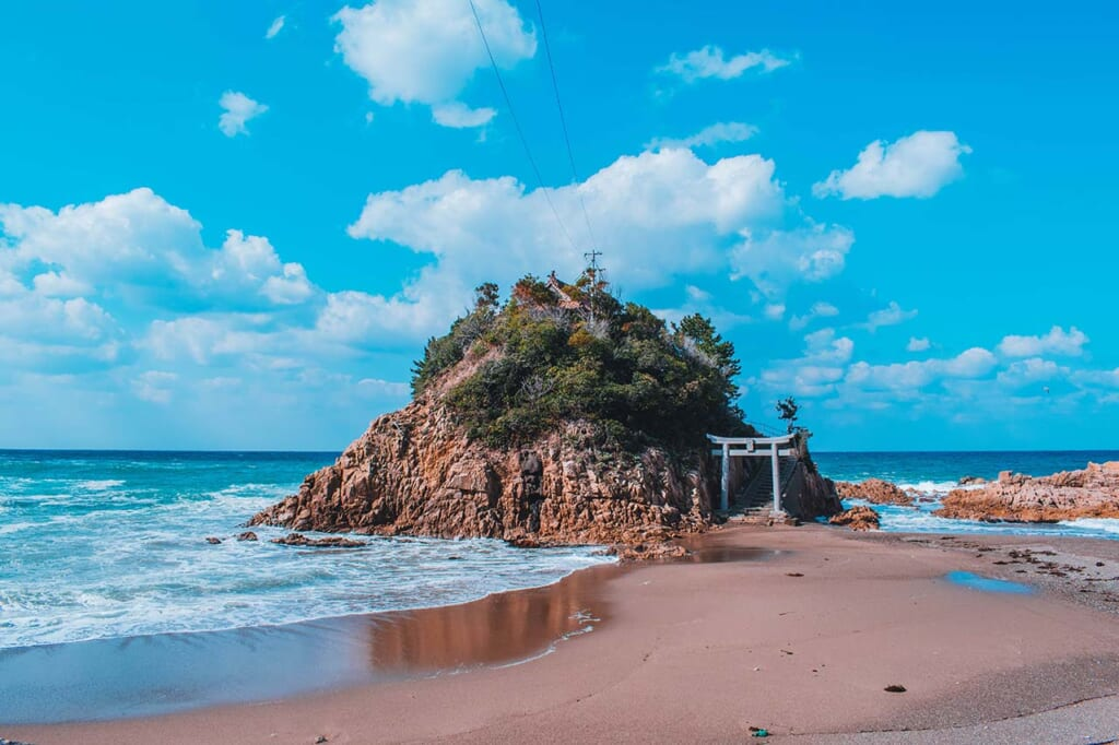 A tiny Japanese island off the coast with a shrine in front of it in Japan