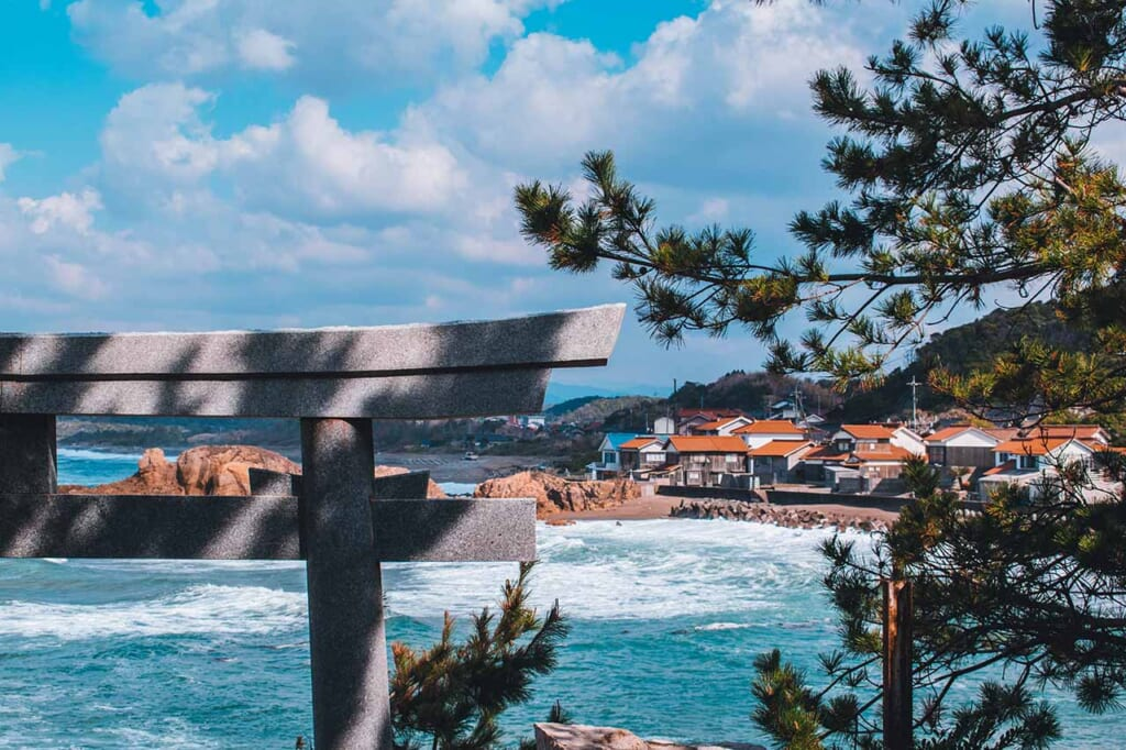 View of the Japanese coastline and orange roofs with part of a Torii gate in the foreground