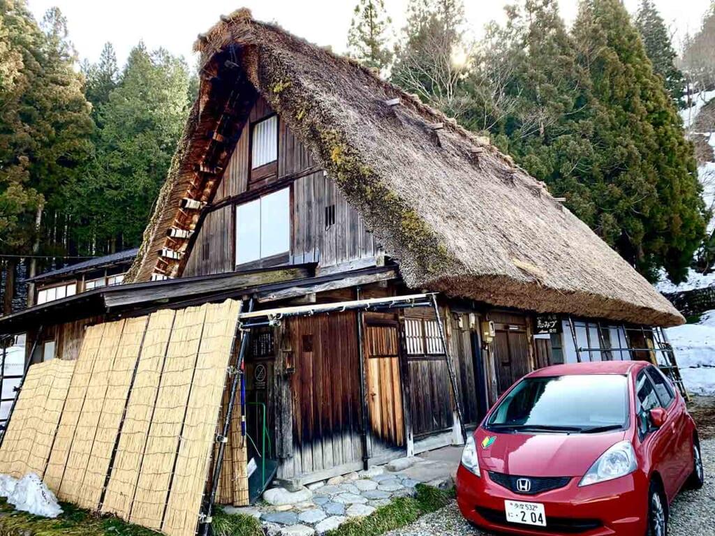 traditional Japanese thatched house next to modern red car at Shirakawa-go, Gifu, Japan