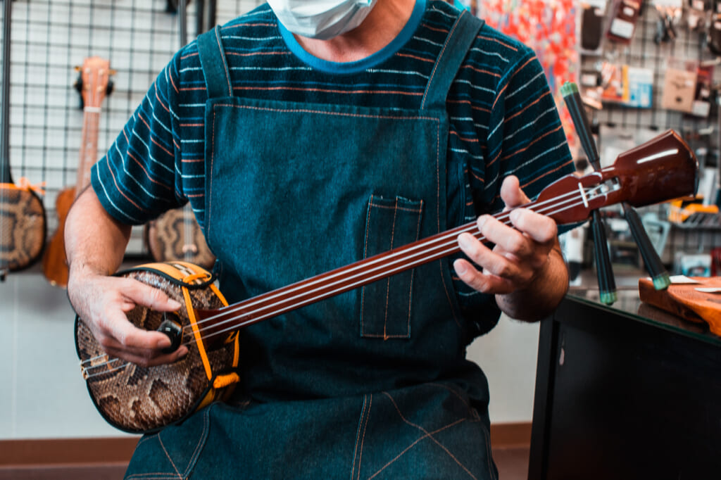 A Japanese man playing a traditional japanese instrument in Okinawa