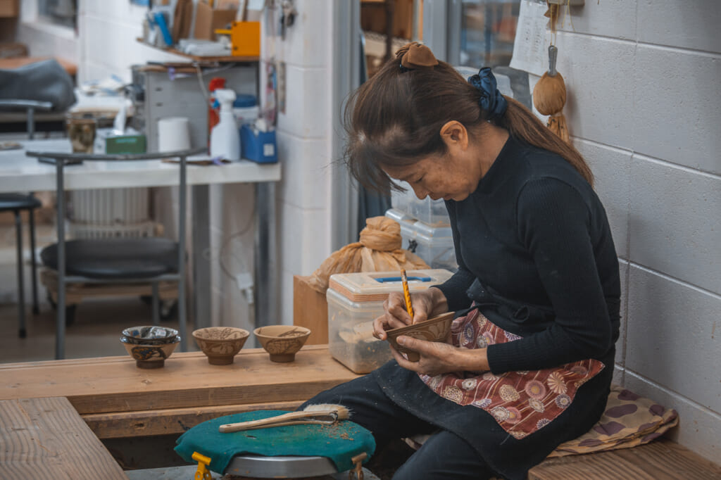 a craftswoman decorating japanese pottery in Okinawa, Japan
