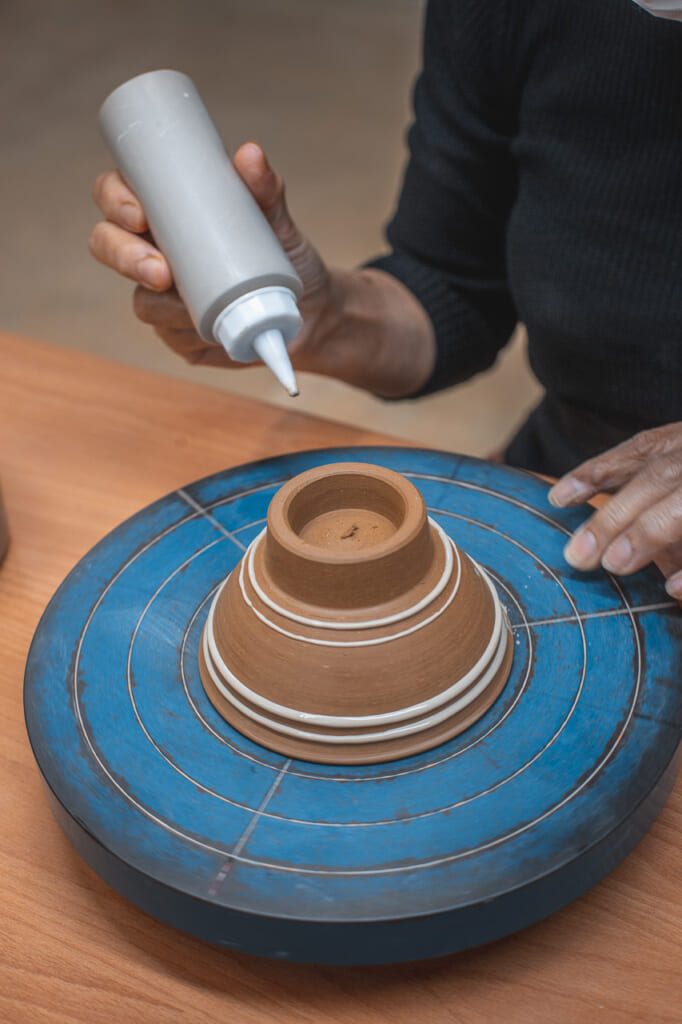 a woman painting a ceramic bowl in Okinawa, Japan