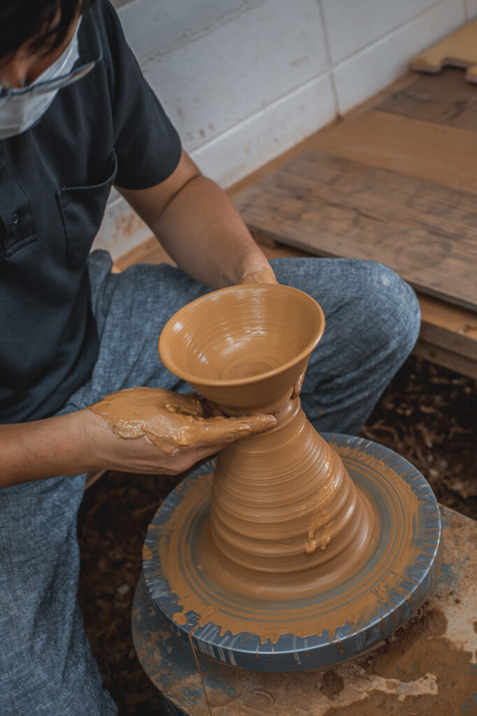 a man using a pottery wheel to make a vase in okinawa, Japan