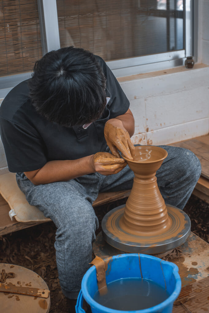 a Japanese craftsmen producing japanese pottery in Okinawa