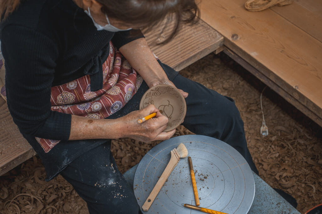 a woman carving a bowl in Okinawa, Japan