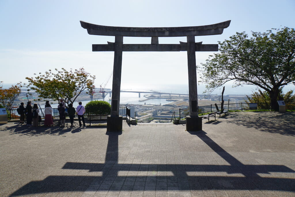 Large Japanese stone torii overlooking bay in Japan