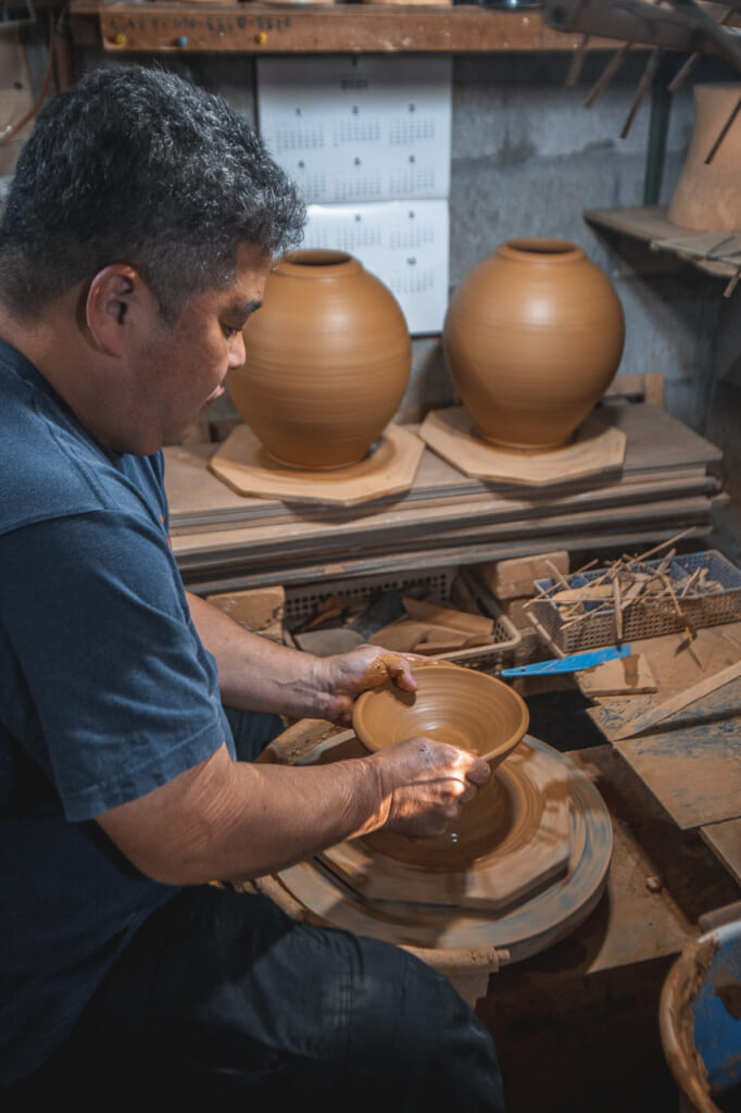 Nakama-san shaping a ceramic plate in the potter's wheel in Okinawa, Japan