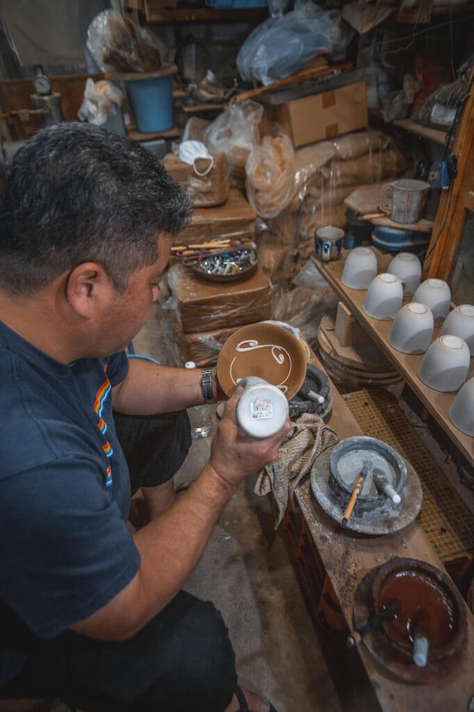 Nakama-san decorating handmade ceramic in Okinawa, Japan