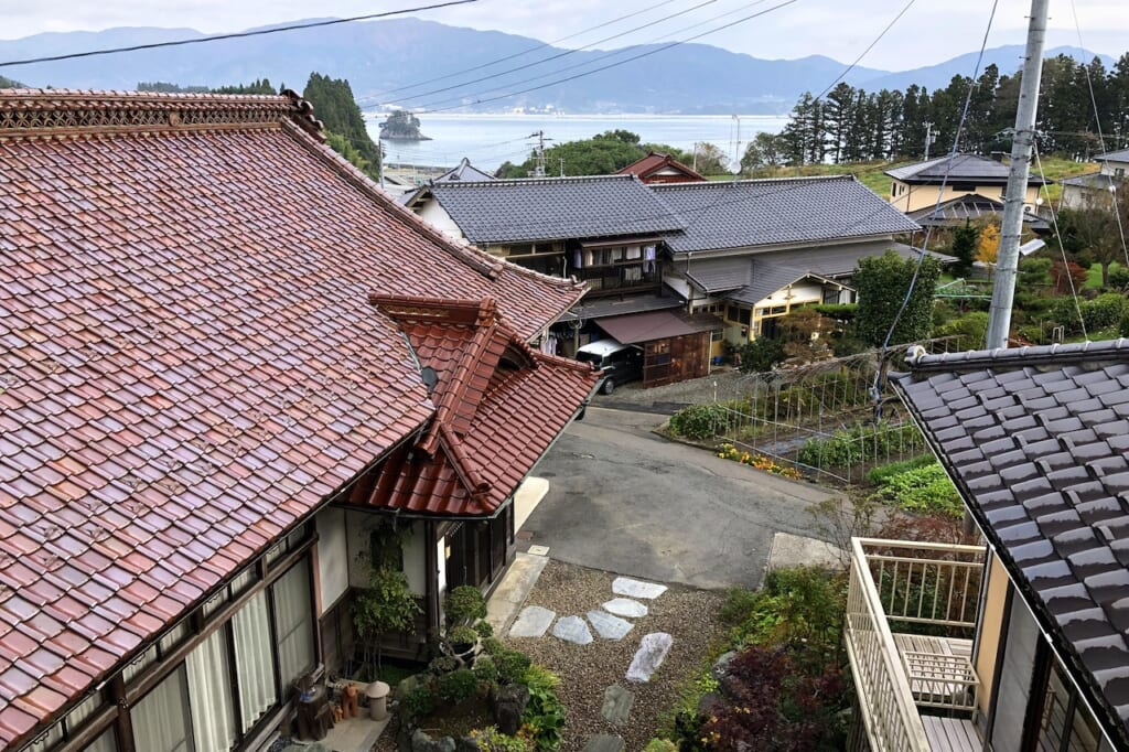 tiled rooftops in front of bay in Japan