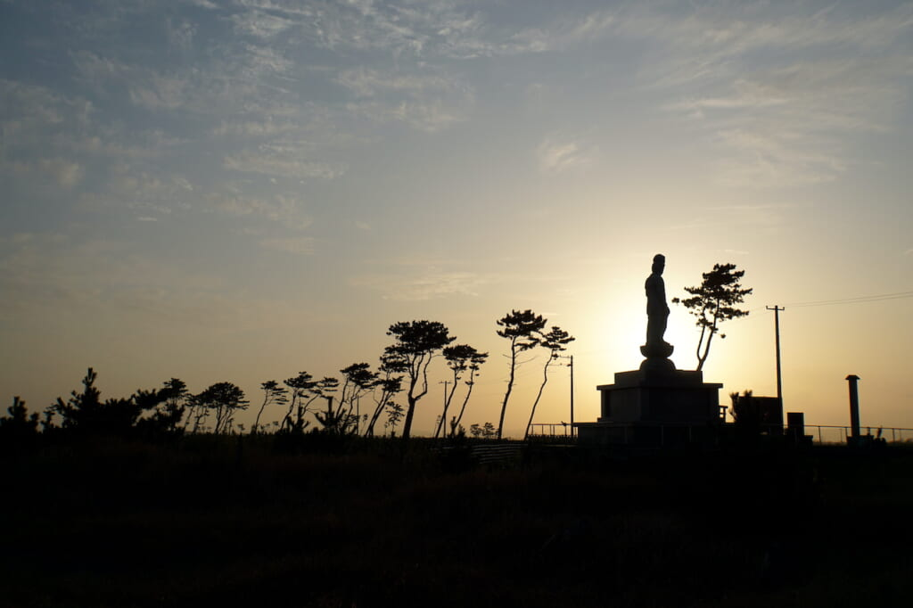 silhouette of Buddha statue and trees at dusk in Japan