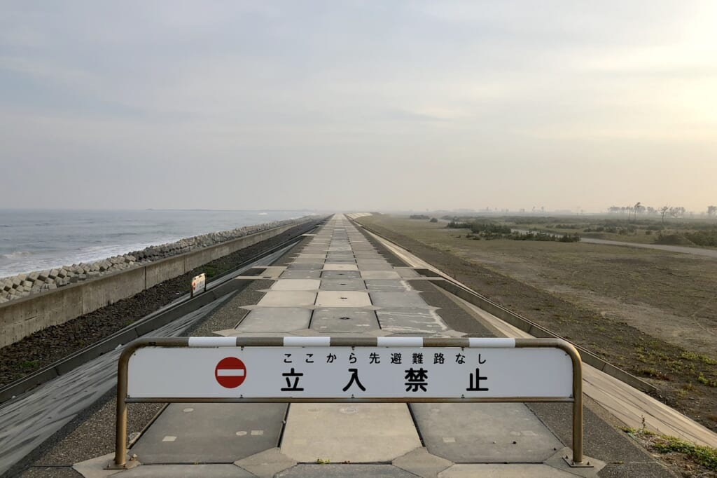 No Entry sign on Japanese seawall stretching out to horizon in Tohoku region of Japan, a lasting memorium of the 2011 Tsunami