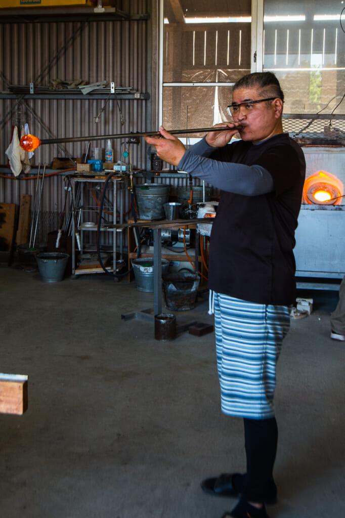 Japanese craftsman, Kaneshi blowing a glass in Okinawa, Japan