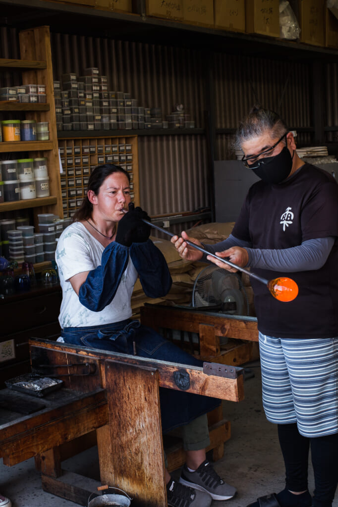 woman blowing a glass in a Japanese glass blowing workshop and studio in Japan