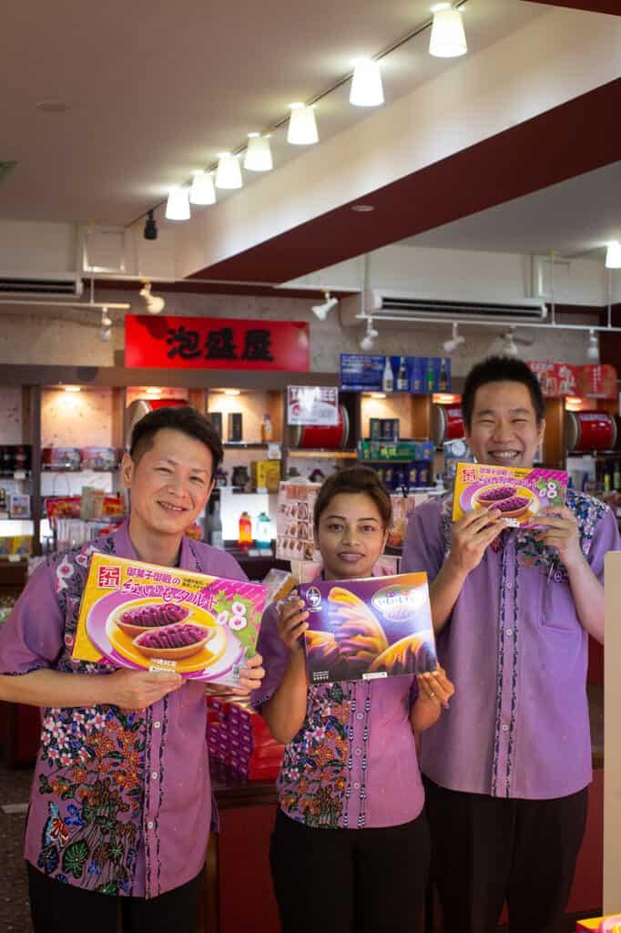 three people showing boxes of benimo tart in Okinawa, Japan