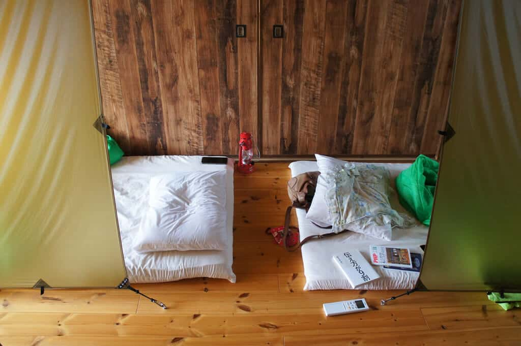 Inside a dormitory with futon mattresses on Manabeshima, a cat island in Japan
