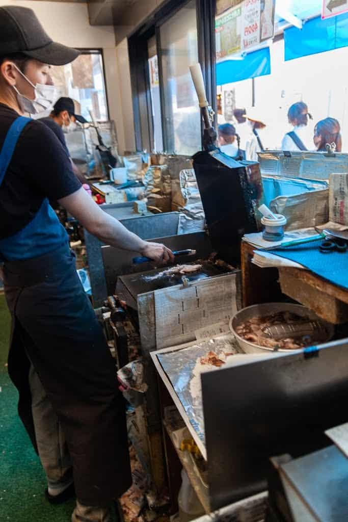 man preparing shrimp on an iron grill in Japan