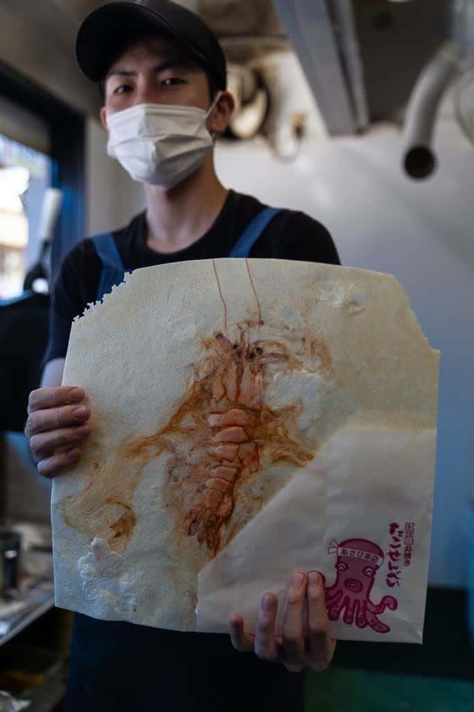 man holding fresh-grilled shrimp rice cracker