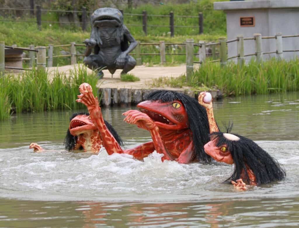 three kappa statues in a pond in japan