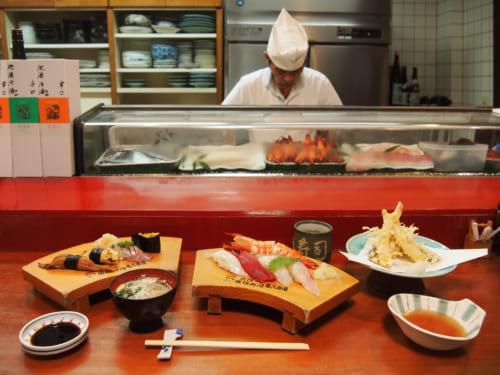 Repas de sushis au comptoir devant le maître à Saiki