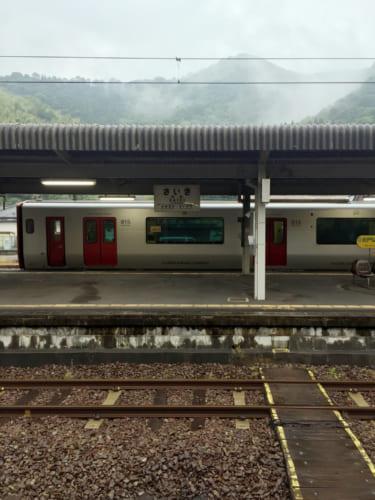 Train dans la gare de Saiki, devant un paysage de montagnes embrumées
