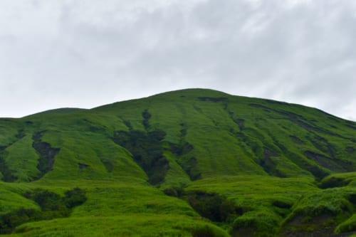 Crevasses sombres sur les pentes verdoyantes du mont Aso